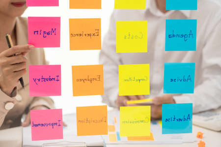 Photo for business people planning startup project placing sticky notes session to share idea on glass wall, Strategy Analysis Office Concept - Royalty Free Image