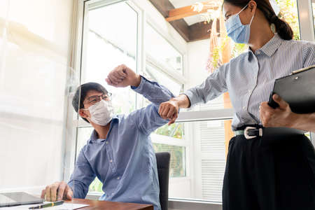 Photo pour Two Asian colleagues in medical masks avoid a handshake when meeting in the office greeting with bumping elbows during coronavirus COVID-19 epidemic in office, Social distancing concept - image libre de droit