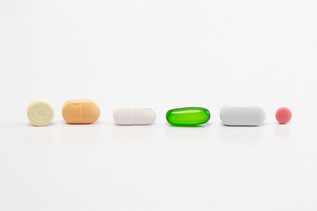 Assorted pills on white background