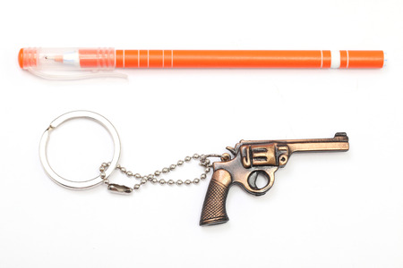 Toy gun with key chain and pen isolated on white background