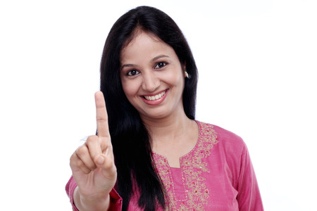 friendly young woman, showing index finger, isolated on white background