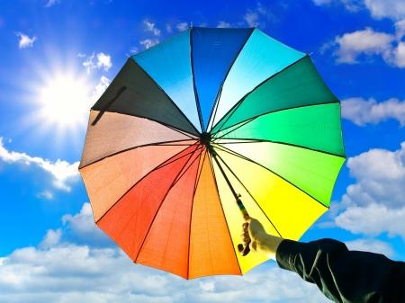 milticolored umbrella in hand against blue sky