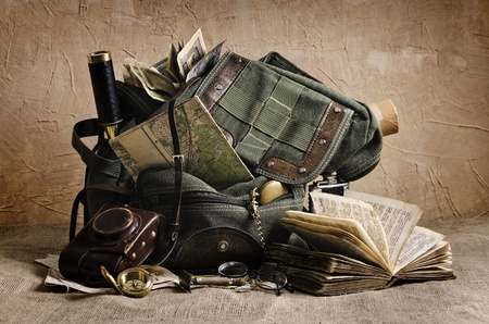 Still life with an old backpack and travel accessories  The elements used for this image  Map - Creation Year 1936  Release of 1940 Book - The Bible on the old Latvian  Release of 18-19 century