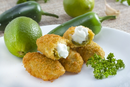 Mexican-american jalapeno poppers served with lime .