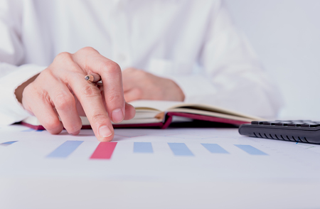 business and financial document  on the table with people using calculator and writing on notebook