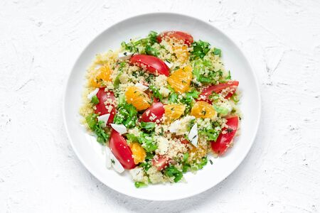 Photo for Healthy and simple food, light summer lunch, fragrant salad with couscous and oranges on a light background - Royalty Free Image