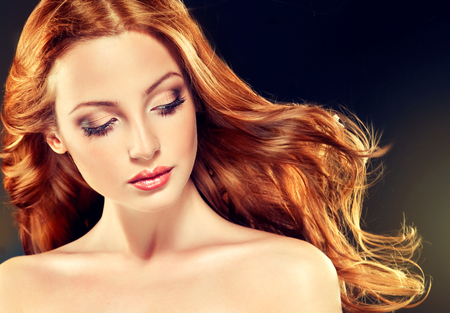 Foto de Beautiful model with long curly red hair .  Styling hairstyles curls - Imagen libre de derechos