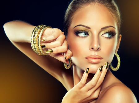 Foto de Beautiful girl with the Golden makeup and gold  metal nails.  Fashion woman Portrait - Imagen libre de derechos