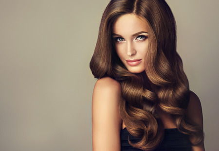 Photo pour Brunette  girl with long  and   shiny wavy hair .  Beautiful  model with curly hairstyle . - image libre de droit