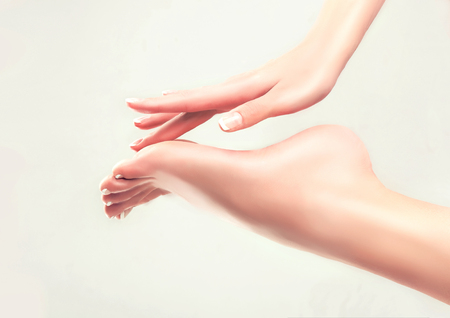 Foto de Beautiful women's hand touches her well-groomed feet. Spa ,scrub and foot care . - Imagen libre de derechos