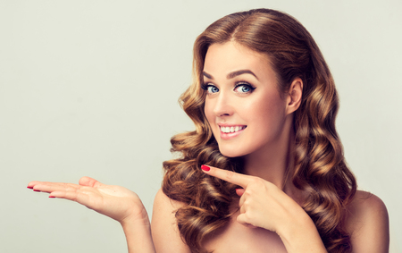 Photo for Surprised woman demonstrates invisible product .Beautiful girl with curly hair pointing to the side. Bright facial expression. - Royalty Free Image