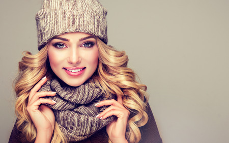 Trendy warm winter clothes. Nice, young,smiling blonde woman dressed in gray wool winter hat and scarf.