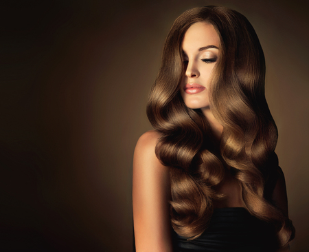Photo for Brunette girl with long and shiny wavy hair . Beautiful model with curly hairstyle . - Royalty Free Image