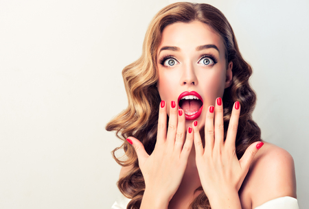 Foto de Extremely astonished and excited young blonde haired model  with wide opened mouth, is looking up above. Shock from happines.Well groomed blond hair and bright red make up and manicure. Image in Pin Up style. - Imagen libre de derechos