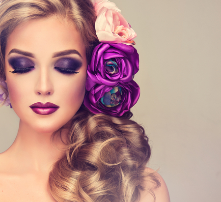 Beautiful model with a big violet and white flowers in her blonde dense curly hairstyle. Makeup smoky eyes. Summer girl with trendy makeup and headdress.