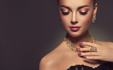 Photo pour Beauty portrait of young gorgeous woman is dressed in a jewelry set of necklace, ring and earings. Pretty  blue eyed model is demonstrating an attractive make up and manicure. - image libre de droit