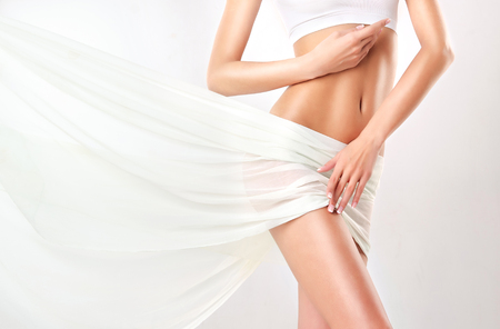 Photo for Part of attractive woman body, hips and slender toned belly, covered by tender, silk textile. Graceful female figure, as a symbol of health and harmony. - Royalty Free Image