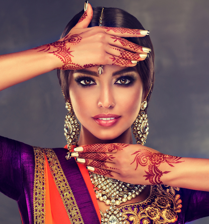 Photo for Portrait of beautiful indian girl dressed in a traditional national suit and  mehndi tattoo is  painted on her hands. - Royalty Free Image