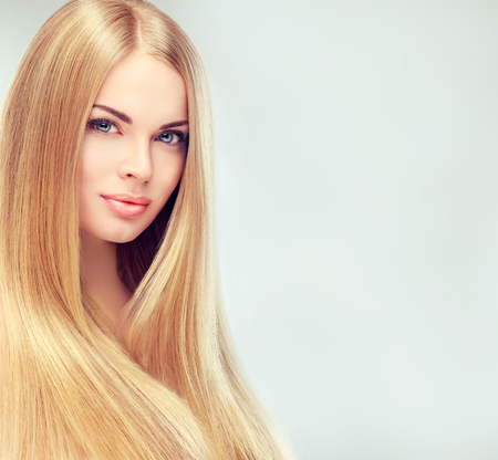Photo pour Young, blonde haired woman  with long, straight, healthy and shiny hair. Beautiful model with long, straight,  hairstyle, delicate make-up and  pale rose lipstick on the lips. - image libre de droit