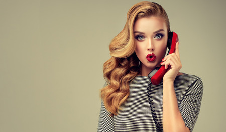 Foto de Expression of shock  and amazement on face of perfectly looked, young, beautiful woman with old fashioned, red phone in her hand. Extremely surprised facial expression. Pin-up style make up, hairstyle and red manicure. - Imagen libre de derechos