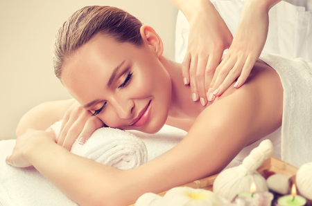 Photo pour Young woman is laying on massage table and gets massage treatment.Spa and body massage.Tender and soft hands of massage specialist is making massage on the back of young and appealing woman. Beauty and Spa treatment concept. - image libre de droit