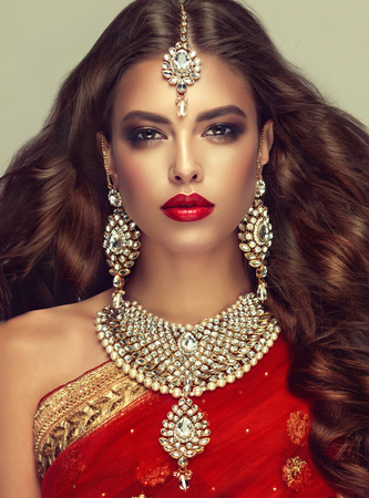 Photo pour Young attractive woman, covered by traditional indian red shawl (dupatta) and dressed in hand-made kundan style jewelry set. Posh jewelry set is consisting of big earrings, bright necklace and head adornment (tikka). Perfect, dense, wavy, freely flying hair and smoky eyes style makeup. - image libre de droit