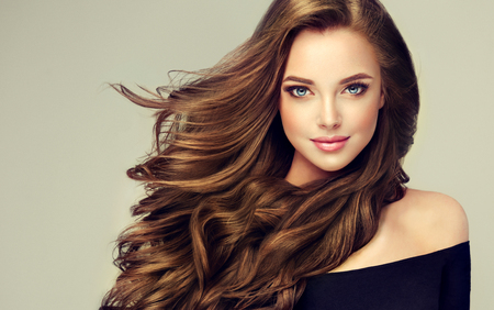 Foto de Young, brown haired woman  with voluminous hair.Beautiful model with long, dense, curly hairstyle and vivid makeup. Perfect dense, wavy,and shiny hair. Hairdressing art, hair care and beauty products. - Imagen libre de derechos