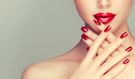 Photo pour Perfect woman lips with ideal shape and colored by bright red lipstick and red manicure on the nails.Stylish evening image for young women. Fashion makeup and cosmetic. - image libre de droit