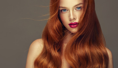 Foto de Young, red haired woman  with soft, kind and tender look at viewers. Irish beauty. Hairdressing art, hair care and beauty products. - Imagen libre de derechos