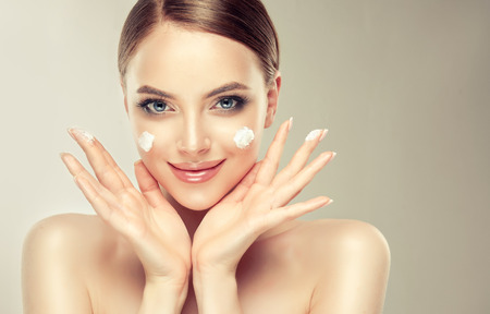 Photo pour Gorgeous, young woman with spots of cosmetic cream on the cheeks. Light smile on the perfect face. Cosmetology. - image libre de droit