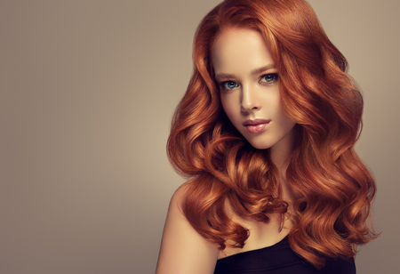 Photo pour Young, red haired beautiful model with long,  curly, well groomed hair. Excellent hair waves. Hairdressing art and hair care. - image libre de droit