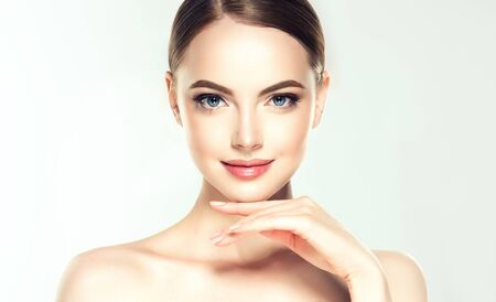 Photo pour Gorgeous, young woman with clean, fresh skin is touching own face. Soft make up and light smile on the perfect face.Facial treatment. - image libre de droit