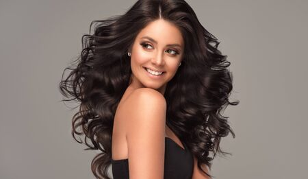 Hairdressing art, hair care and beauty products. Happy,toothy smile on the pretty face of young, brown haired woman with voluminous hair. Beautiful model with long, dense, curly hairstyle and vivid makeup.