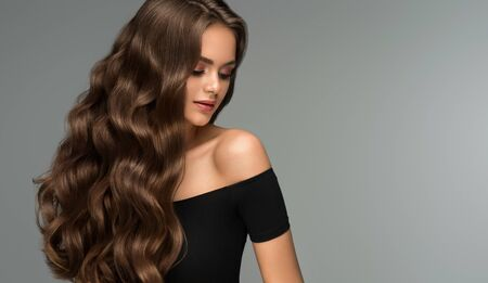 Young, brown haired woman with voluminous hair. Perfect dense, wavy,and shiny hair. Hairdressing art, hair care and beauty products.
