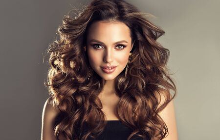 Photo pour Beautiful model with long, dense, curly hairstyle and vivid makeup. Bold and dazzling look of beautiful lady. Hairdressing art, hair care and beauty products. - image libre de droit