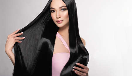 Photo pour Black haired young woman with asian appearance is demonstrating dense, well cared, straight hair and vivid evening makeup on the face.Oriental beauty. Hairdressing art, hair care and beauty products. - image libre de droit