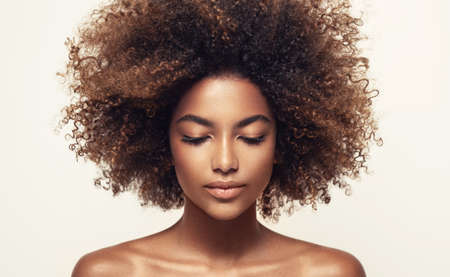 Photo pour Calmness and inner concentration on the face of young beautiful woman. Natural, dense afro hair on the head brown skinned model. Girl with vibrant, melanin-rich skin tone. Beauty of youth. - image libre de droit