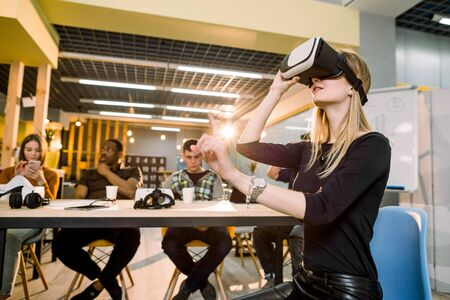 Photo pour Pretty female business woman in black wear trying 3d vr glasses at work. Multiracial team of young people working together in creative office - image libre de droit