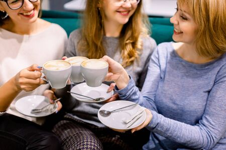 Photo pour Drinking coffee together. Top view of tree beautiful women keeping cups of coffee in hands and smiling. Women in cafe indoors. Meeting of best friends. Coffee with cakes - image libre de droit