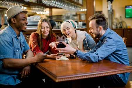 Photo pour Portrait of cheerful young friends looking at smart phone while sitting in cafe. Mixed race people sitting at a table in restaurant using mobile phone - image libre de droit