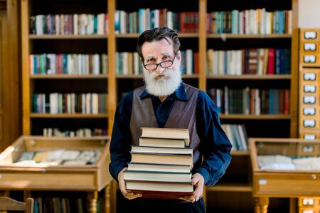 Photo pour Portrait of positive smart old bearded man in dark shirt and leather vest, library worker, teacher, working in library, holding stack of books while standing over book shelves background. - image libre de droit