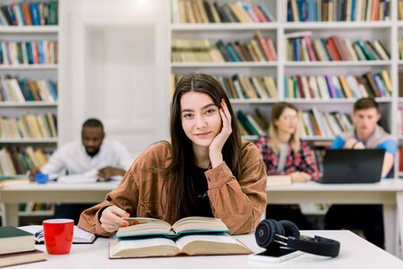 Photo pour Young beautiful girl with straight long dark hair wearing in brown shirt, sitting at the table in library and preparing for test or exam, reading books. Girl posing on camera with smile - image libre de droit