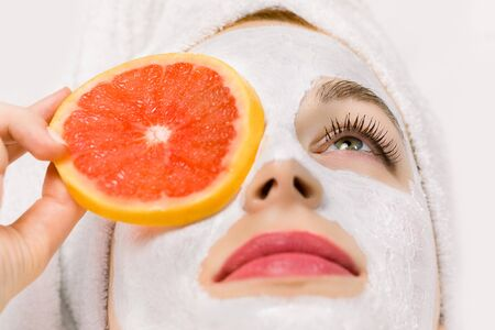 Foto de Face fruit peeling mask, spa beauty treatment, skincare. Young woman getting facial care at spa salon, mud clay mask on her face, holding slice of grapefruit hiding her eye. Close-up, macro photo - Imagen libre de derechos