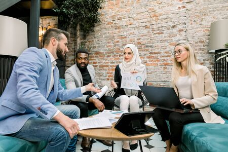 Photo pour Multiethnic business people on the meeting in office. Arabian business lady in white hijab using financial document with graphs talking to her male and female partners about the results of research - image libre de droit