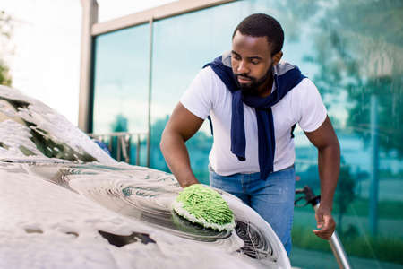 Photo pour Young attractive African American man washing his modern electric luxury car in a self-service car wash station outdoors with cleaning foam and green sponge mitten - image libre de droit