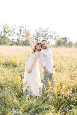 Photo pour Family, motherhood and pregnancy concept. Happy couple waiting for a baby in sunny day, standing back to back in the field - image libre de droit