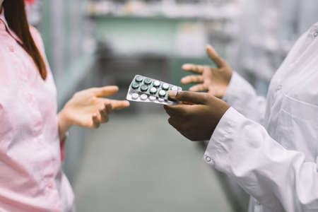 Photo for Unrecognizable African pharmacist and female customer in drugstore. Hand of woman taking pill blisters, buying in pharmacy. Chemist giving pill blisters to her patient - Royalty Free Image