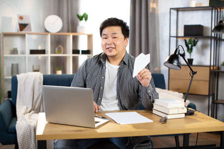 Photo for Smiling asian freelancer playing with paper plane - Royalty Free Image