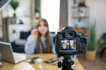 Photo for Popular caucasian blogger testing new cosmetics for advertisement during live broadcast. Young woman sitting at table and looking at camera that fixed on tripod. - Royalty Free Image