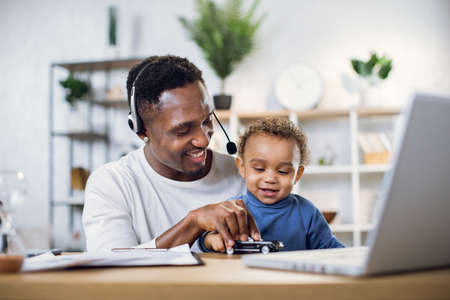 Photo pour Afro american father in headset playing with cute son and conducting online meeting on modern laptop. Young man sitting at home with baby boy and working on distance. - image libre de droit